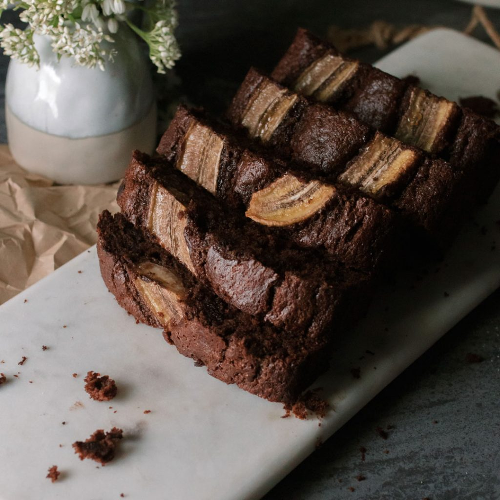 Double Chocolate Banana Bread cut into slices, with pieces leaning against each other on a cutting board.