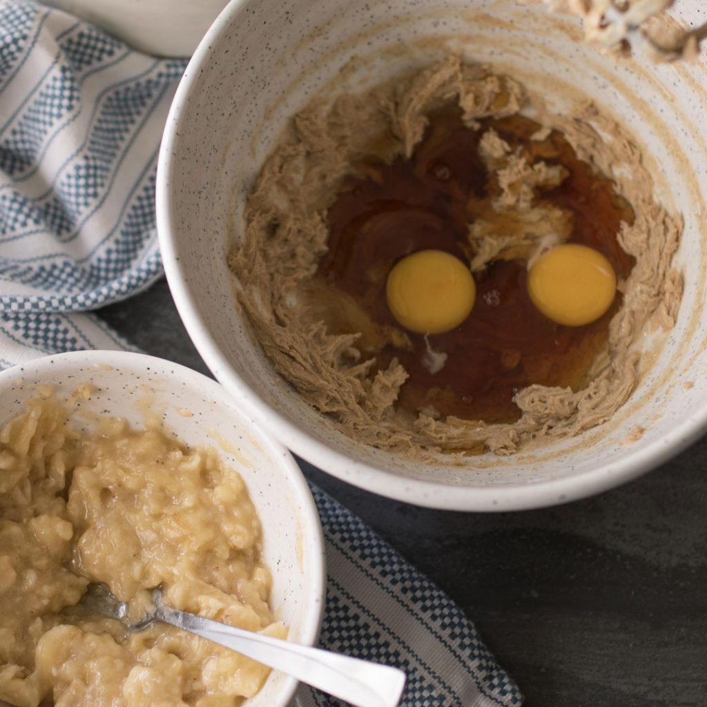 Two mixing bowls with mashed banana and a focus on eggs ready to be beaten into mixed brown sugar and butter.