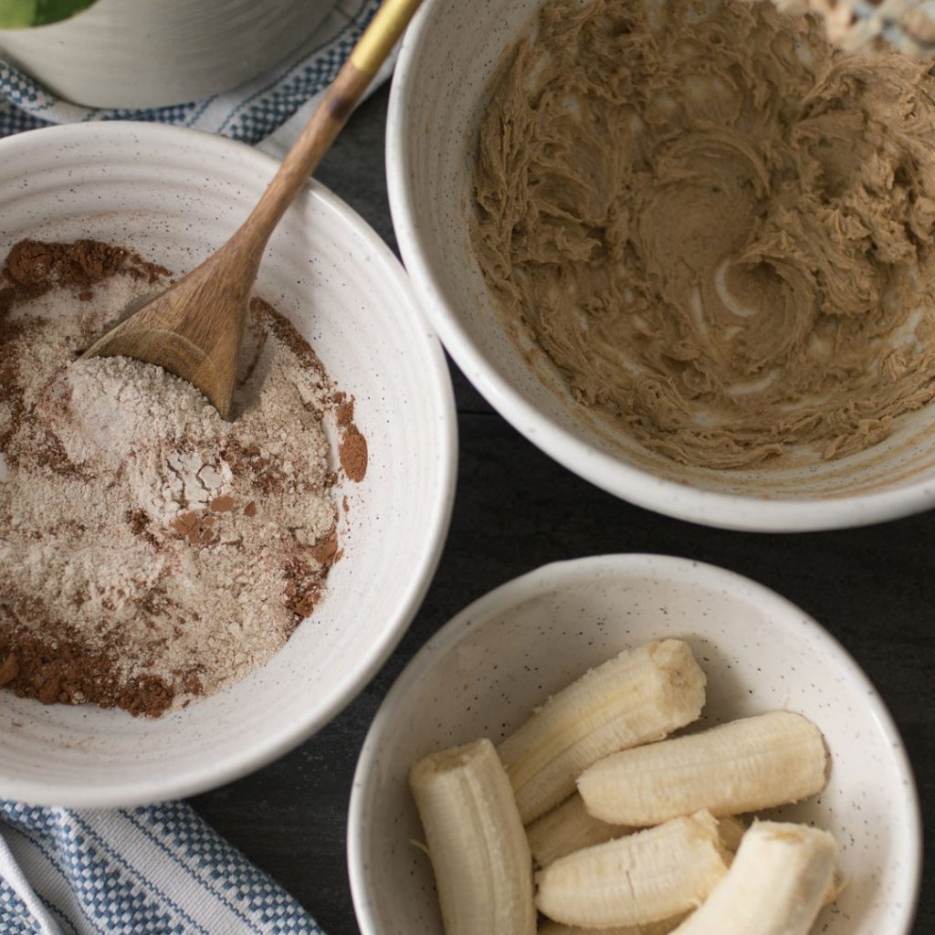 Bowls of ingredients with a focus on the dry ingredients that include flour, baking soda, cocoa powder and salt.