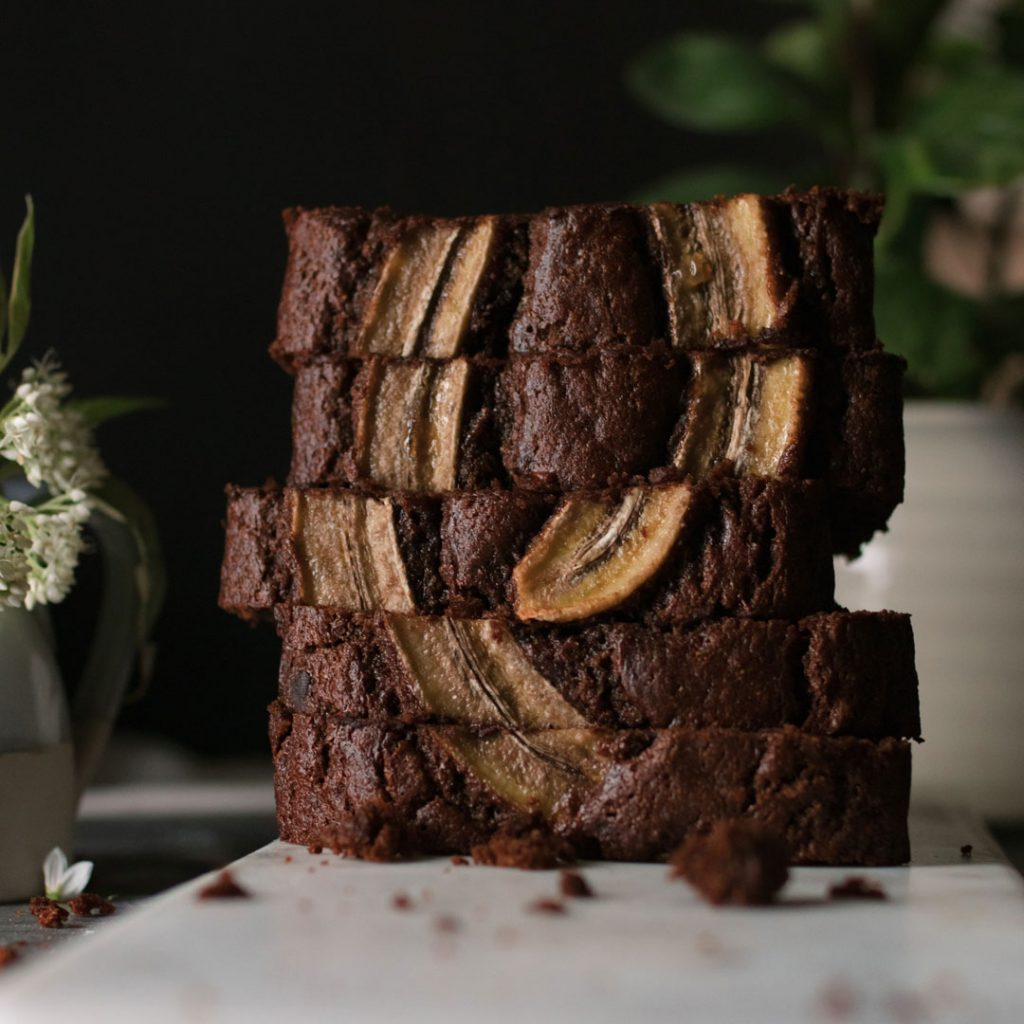 Double Chocolate Banana Bread stacked on it's side on a cutting board.