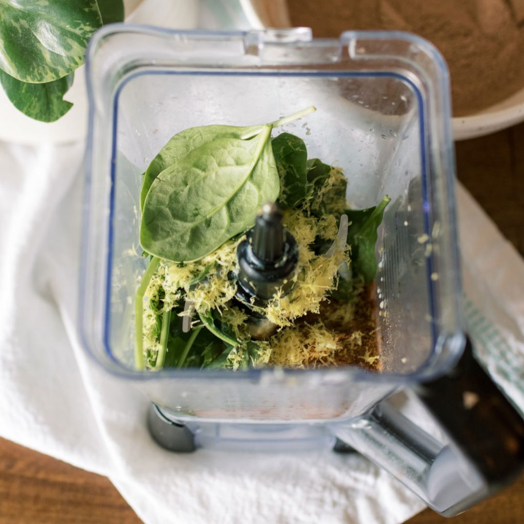 Ingredients with spinach and lemon zest in a blender container to make green smoothie muffins.