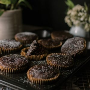 A group of green smoothie muffins in paper cups in a baking sheet.